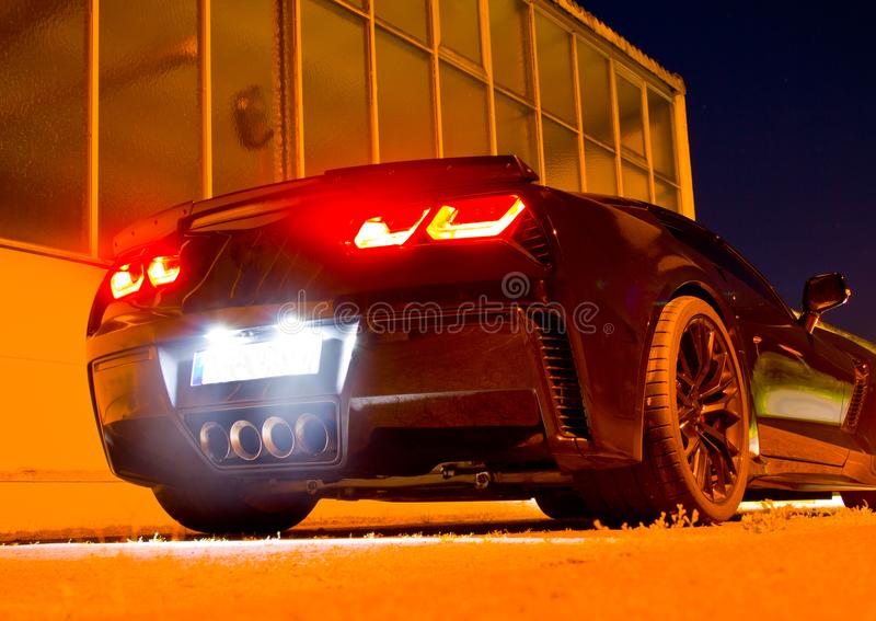 US sports car at night with glowing taillights stock photo