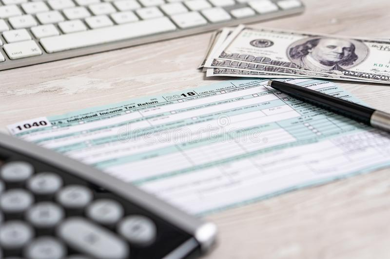 US tax form 1040 with pen, calculator and dollar bills. tax form law document usa white business concept royalty free stock image