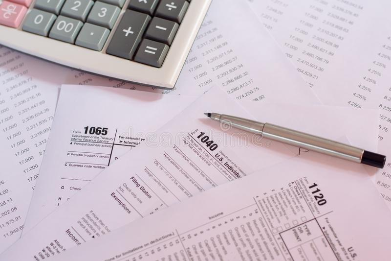 US tax form with pen and calculator selective focus / taxation c. Oncept stock photography