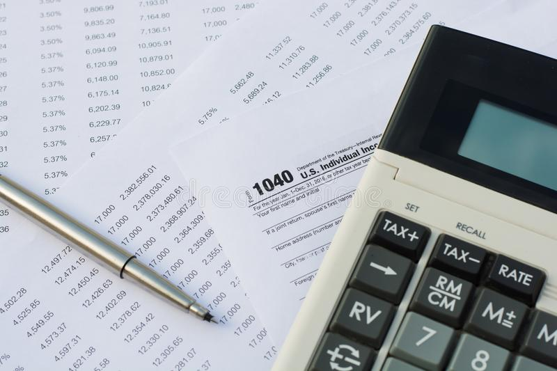 US tax form with pen and calculator selective focus / taxation c. Oncept stock images