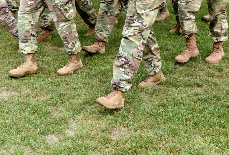 US troops. Soldiers marching on green grass. US Army stock photography
