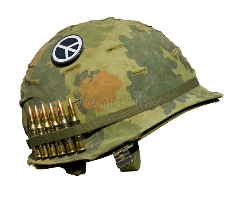 US Vietnam War Helmet - Peace Button. A US military helmet with an M1 Mitchell pattern camouflage cover from the Vietnam war, with six rounds of 7.62mm stock photo