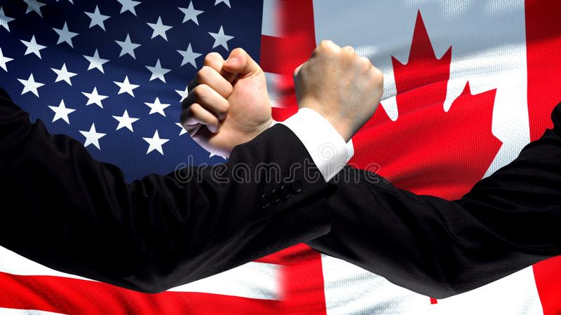 US vs Canada confrontation, countries disagreement, fists on flag background. Stock photo stock image