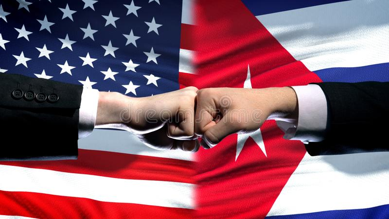 US vs Cuba conflict, international relations crisis, fists on flag background. Stock photo royalty free stock photos