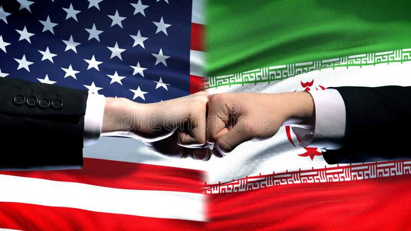 US vs Iran conflict, international relations crisis, fists on flag background. Stock photo stock photo