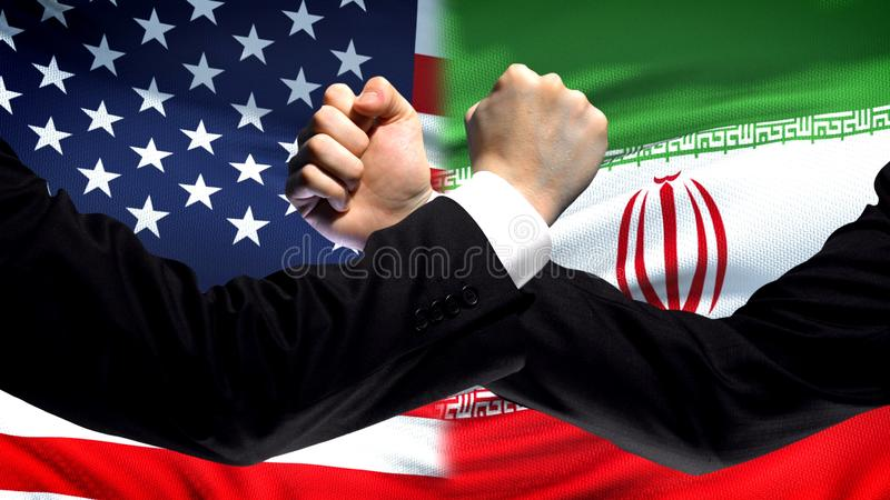 US vs Iran confrontation, countries disagreement, fists on flag background. Stock photo stock photo