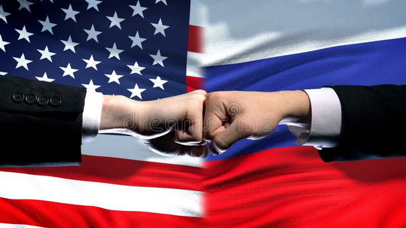 US vs Russia conflict, international relations crisis, fists on flag background. Stock photo royalty free stock image