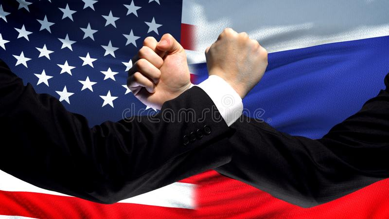 US vs Russia confrontation, countries disagreement, fists on flag background. Stock photo stock images