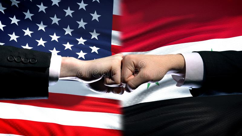 US vs Syria conflict, international relations crisis, fists on flag background. Stock photo stock photo
