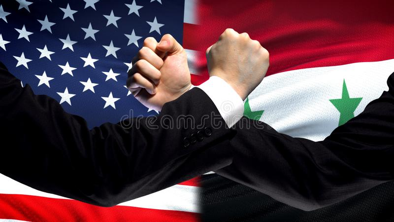 US vs Syria confrontation, countries disagreement, fists on flag background. Stock photo royalty free stock photo