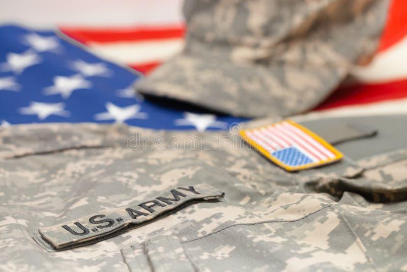 USA armélikformig som ligger över nationsflaggan - studioskott arkivbild