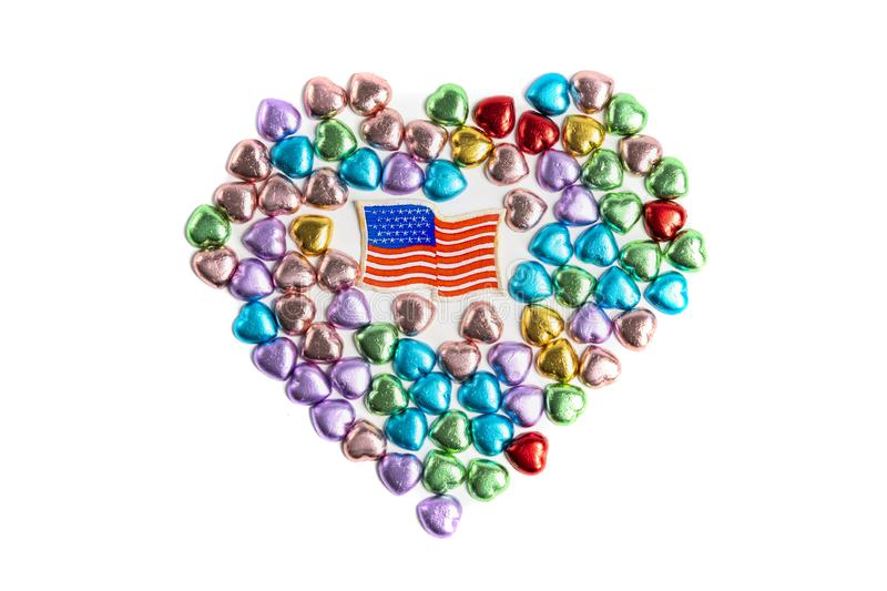A USA badge and heart shape candies. An old USA cloth flag badge in the middle of colorful heart shaped chocolate candies on white background.  July 4th stock images