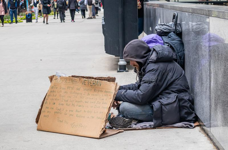 Homeless man with a cardboard sign, begging, downtown. USA, Chicago, Illinois. May 9, 2019. Homeless veteran sitting on the roadside holding a cardboard sign stock photo