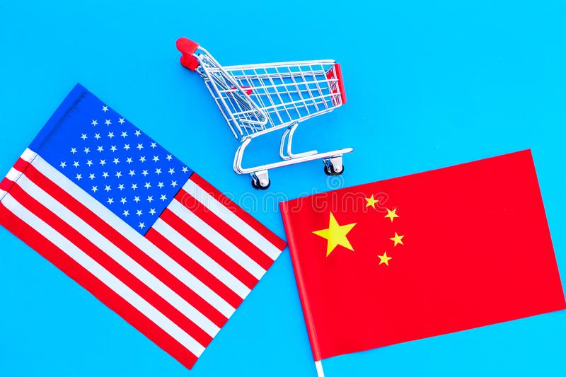 USA and China trade war. American and chinese flags near shopping chart on blue background top view.  royalty free stock images