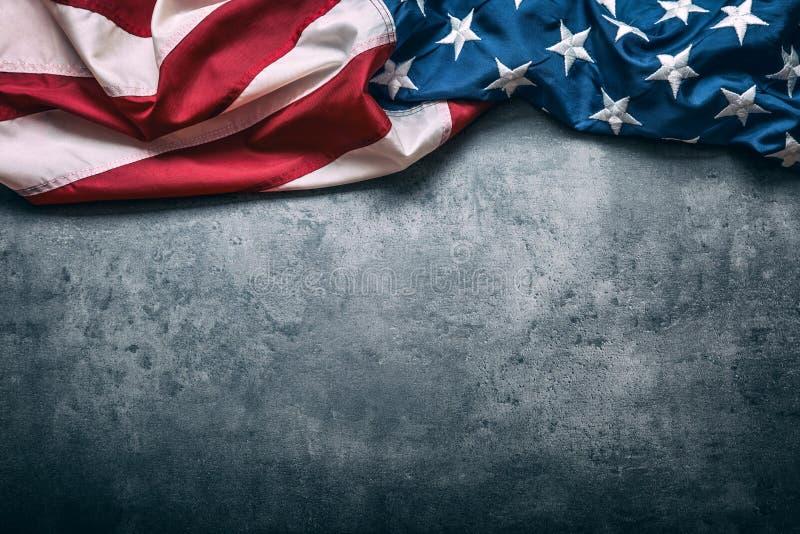 USA flag. American flag. American flag freely lying on concrete background. Close-up Studio shot. Toned Photo stock image