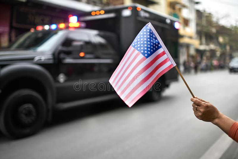 Citizen with flag welcomes diplomatic escort car passage. USA flag in a female hand on the blurred background of the moving car with flashing lights of the stock photo