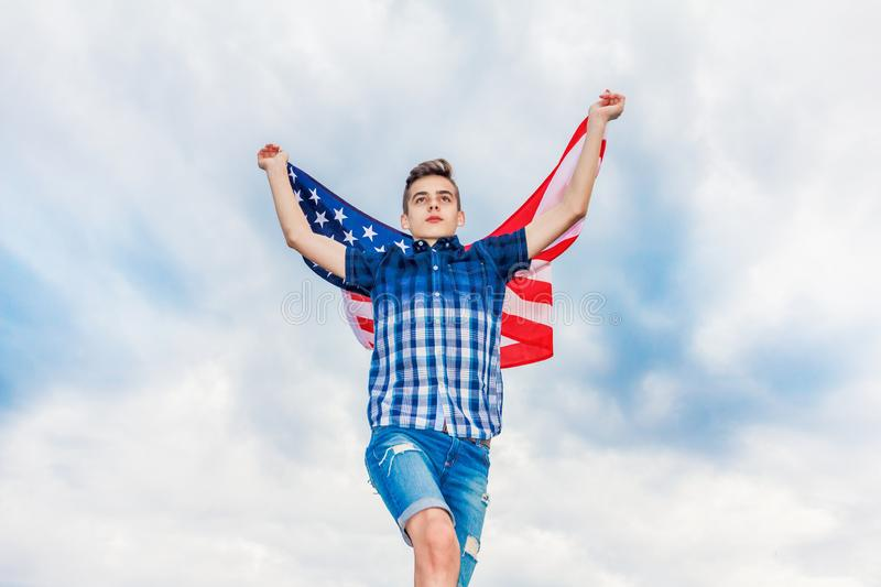 USA flag is held by a running guy in the background of a summer sky royalty free stock photos