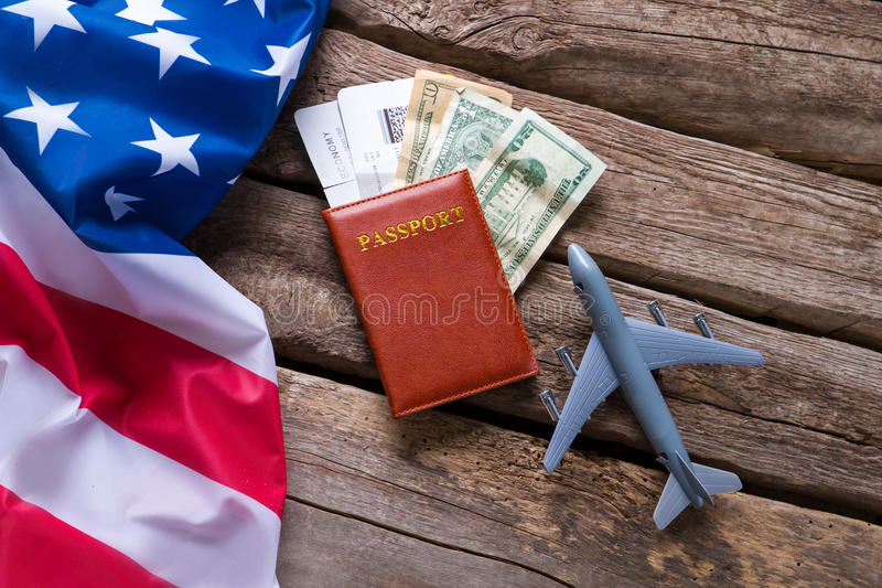 USA flag and a passport. Toy airplane near dollar bills. Visa for trip to America. Chance which costs a fortune stock photos