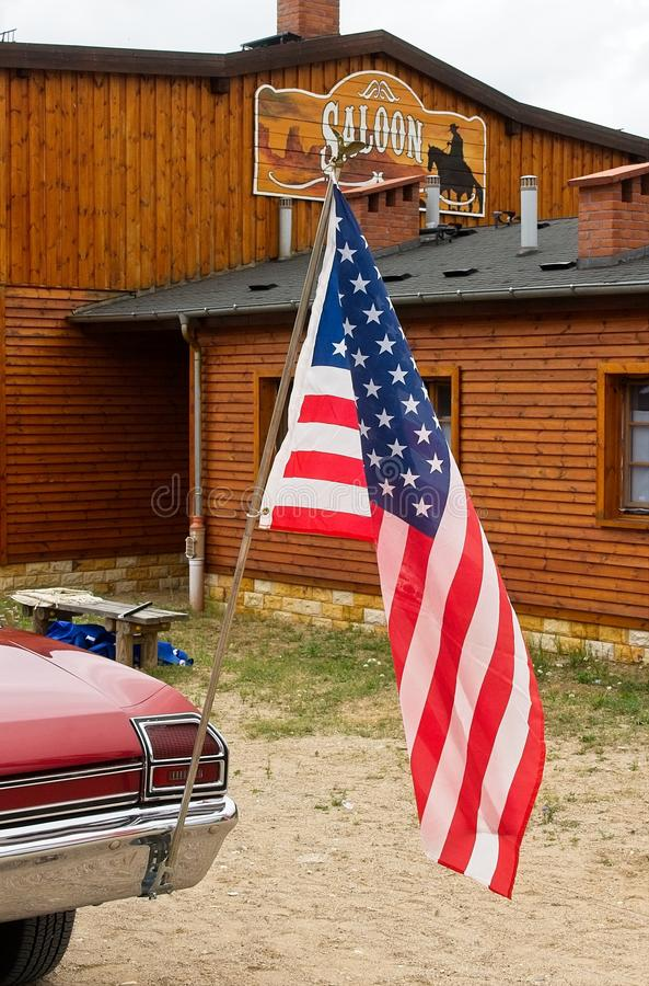 USA Flag. Star spangled banner on car parked next to saloon royalty free stock images