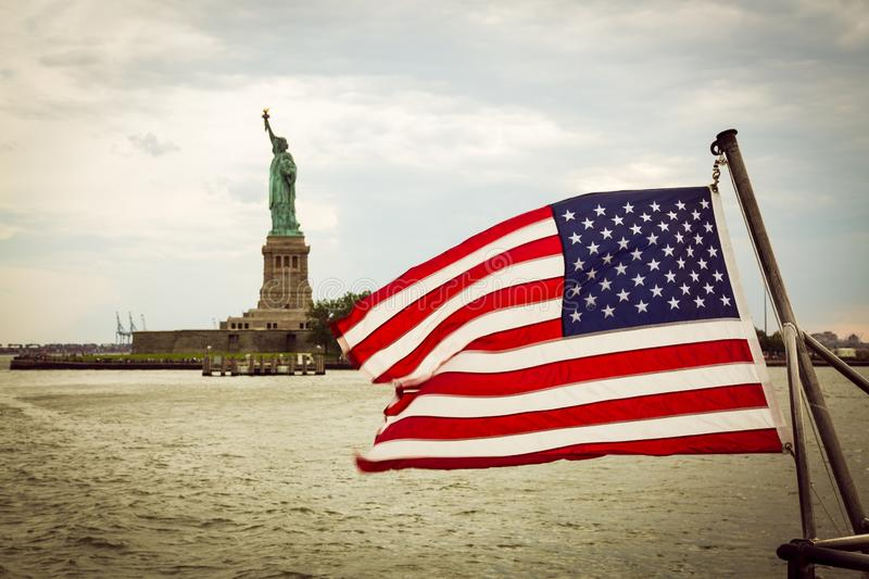 USA flag and Statue of Liberty in the background, New York royalty free stock photos