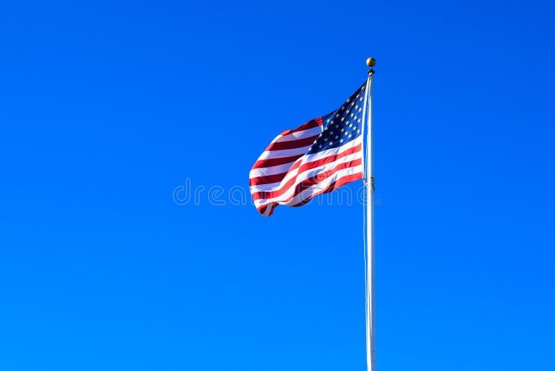 USA Flag Waving on a High Quality Clear Blue Sky stock image