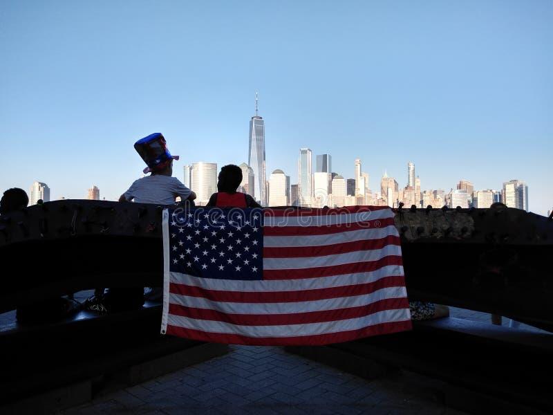 USA flagga, amerikanska flaggan, New York City horisont, One World Trade Center, fjärdedel av Juli, 9/11 minnesmärke, Jersey City royaltyfri fotografi