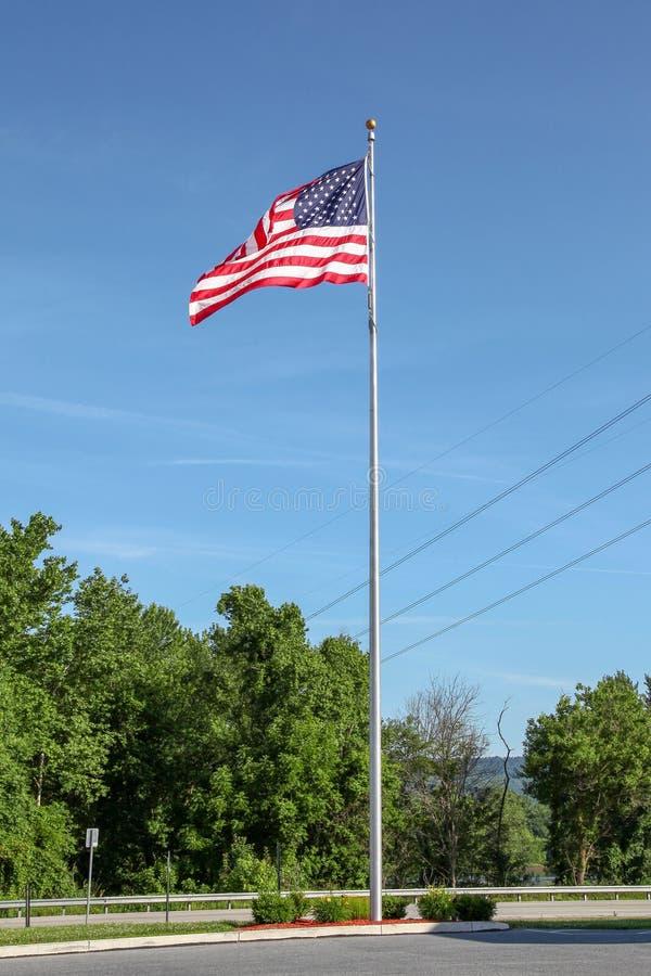 USA flagga på pol i blå himmel på USA arkivbild
