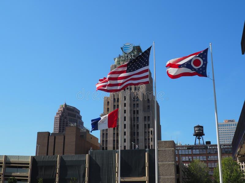 USA-flaggan flyger proudly framme av flaggan av Ohio och staden av Cleveland Flag i den ljusa solen arkivbild