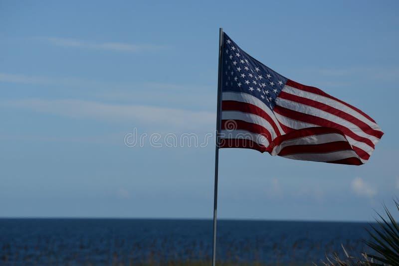 USA flaggan tillfogar en patriotisk signalljus till en fridsam strandstad på den atlantiska kusten royaltyfria foton