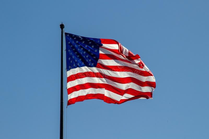 USA flagi amerykańskiej falowanie w wiatrze na jasnym niebieskim niebie w tle zdjęcie royalty free