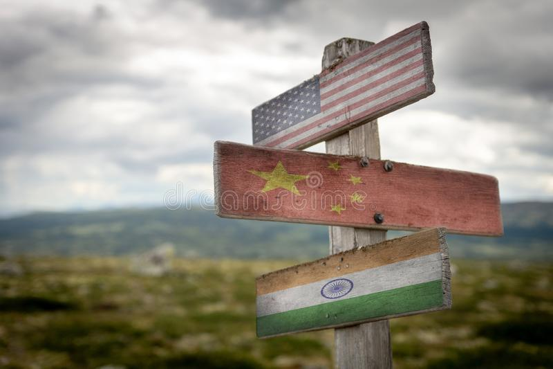 Usa, India and China national flags on wooden signpost outdoors in nature. Usa, China and India national flags on wooden signpost outdoors in nature. Three stock images