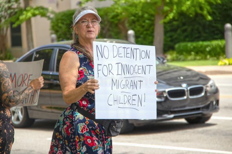 USA ingen försening för oskyldiga flyttande barn - den äldre kvinnan i nätt klänning och sunhat rymmer tecknet på samlar med arkivfoto