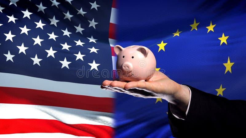 USA-investering i EU, affärsmanhand som rymmer piggybank på flaggabakgrund royaltyfri fotografi