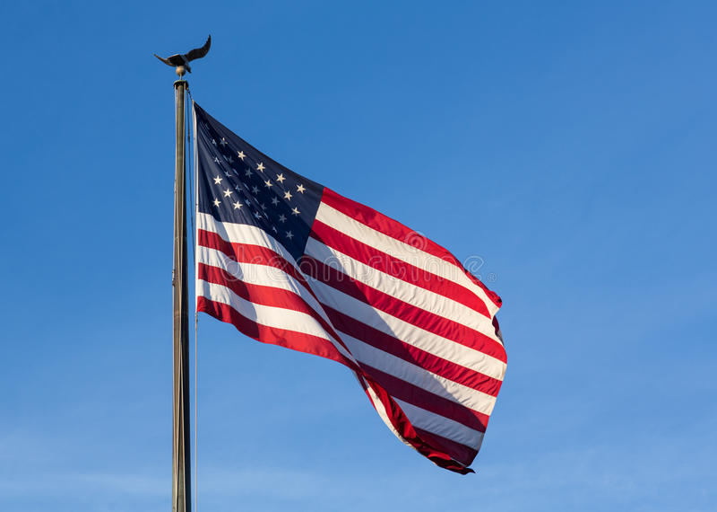 USA lampasów i gwiazd flaga przeciw niebieskiemu niebu zdjęcia stock