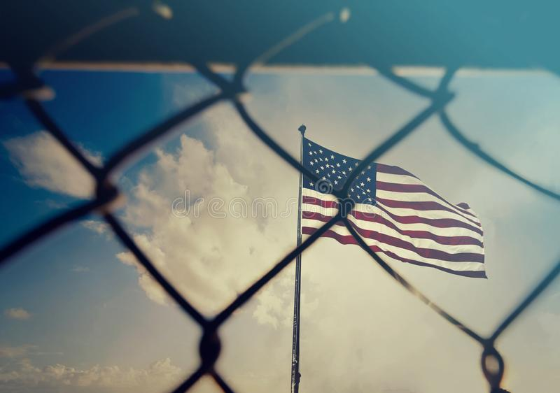 USA and migration border fence. US of America flag behind a steel wire mesh royalty free stock photos