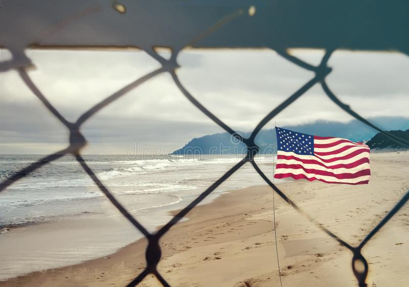 USA and migration border fence. US of America flag behind a steel wire mesh stock photography