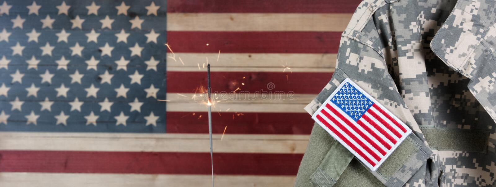 USA military uniform with rustic wooden flag of United States of. Military uniform with United States of America patch flag and burning sparkler in background on stock images
