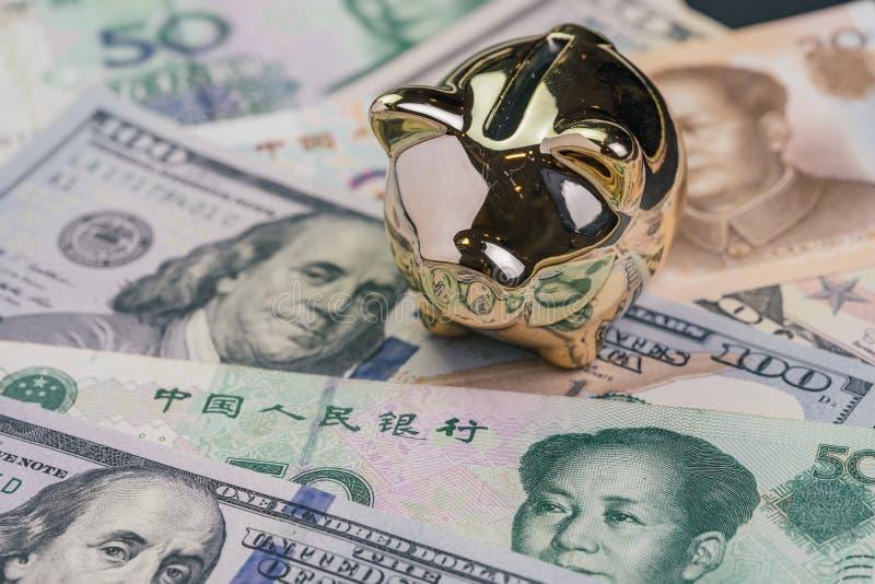 USA och Kina handlar krig- och f?r tarifff?rhandling begrepp, den guld- spargrisen p? F?renta staterna Amerika och kinesiska sedl arkivbilder