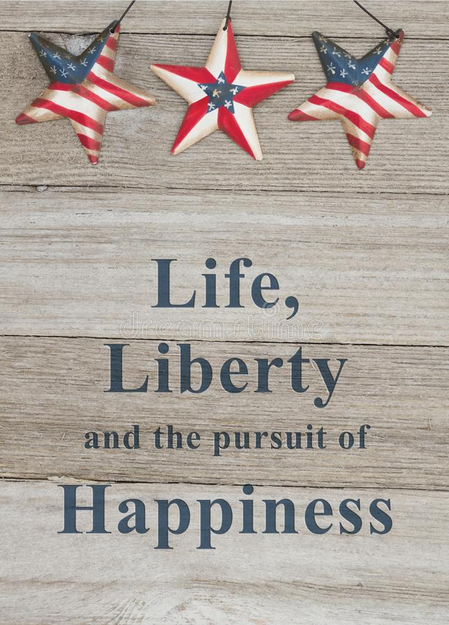USA patriotic message of life liberty and happiness. USA patriotic message, USA patriotic old flag on a stars with weathered wood background with text Life royalty free stock images