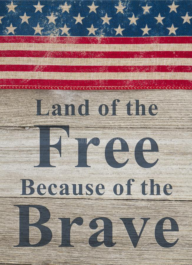 USA patriotic message. USA patriotic old flag on a weathered wood background with text Land of the Free Because of the Brave stock photos