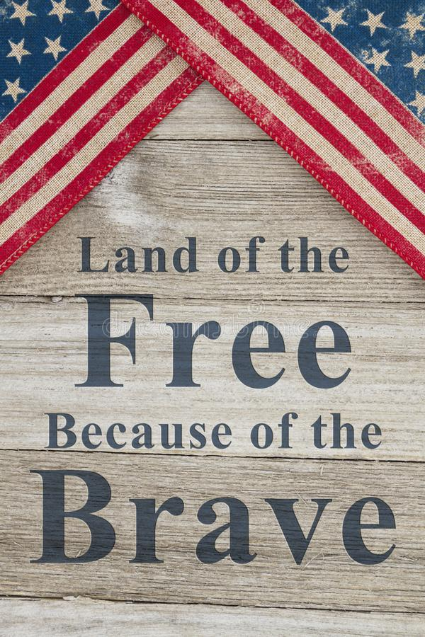 USA patriotic message. USA patriotic old flag on a weathered wood background with text Land of the Free Because of the Brave stock image