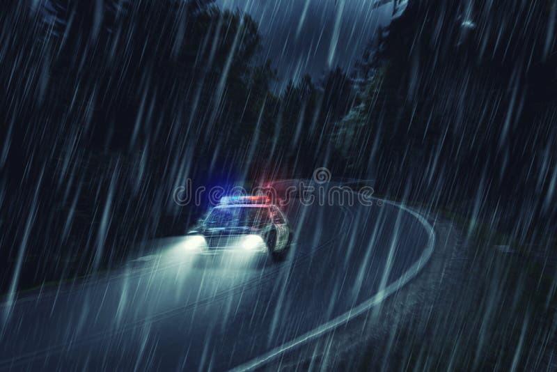 USA polisbil på arbete på natten i skogen, hällregn, motio royaltyfri foto