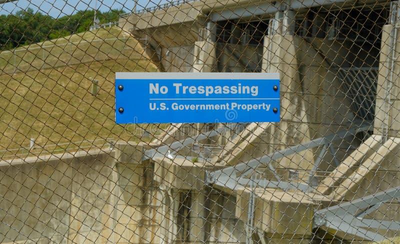 USA:s regering har inga inkräktande skyltar som lagts ut om trådstängsel som begränsar tillgången till en damm royaltyfri fotografi