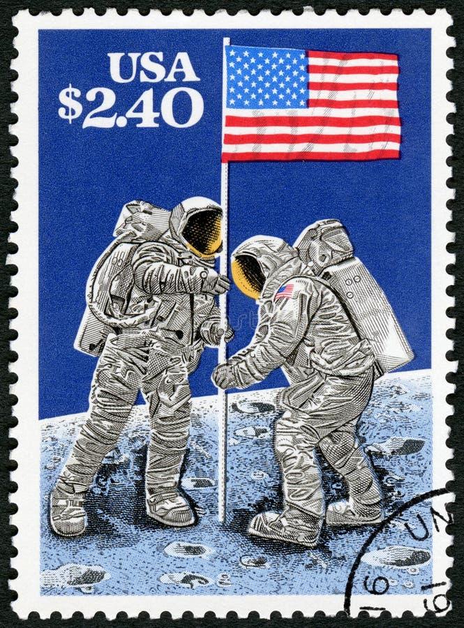 USA - 1989: shower som lyfter flaggan på mån- yttersida, Juli 20, 1969, månelandning, 20th årsdag arkivbild