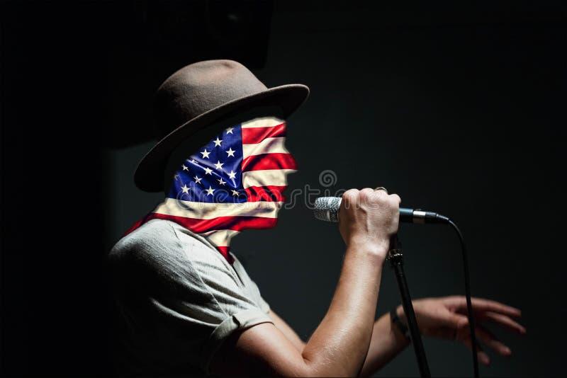 USA-självständighetsdagen Begreppet: propaganda av den amerikanska livsföringen, patriotism Personen talar in i mikrofonen, Uen arkivbild