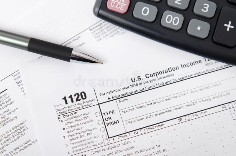 USA-skattform 1120 med pennan och räknemaskinen royaltyfria foton