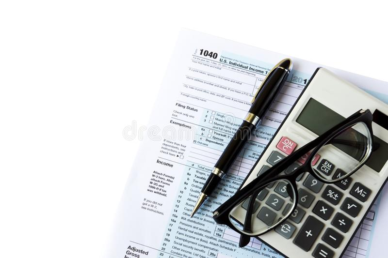 USA Tax Filing. Tax filing - Top view of calculator, pen, eyeglasses and out of focus U.S IRS 1040 form royalty free stock photos