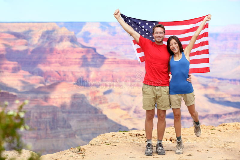 USA travel tourist couple holding american flag. In Grand Canyon. Happy young multiethnic couple cheering at Grand Canyon south rim during summer holidays royalty free stock images