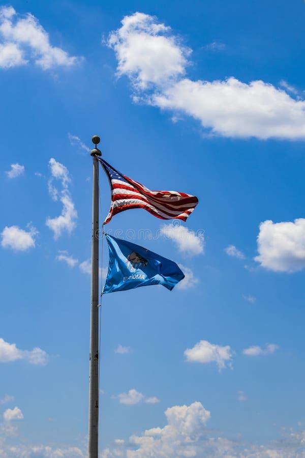 USA und Oklahoma-Flaggen, die gegen einen sehr blauen Himmel mit flaumigen weißen Wolken an einem windigen Tag fliegen stockbild