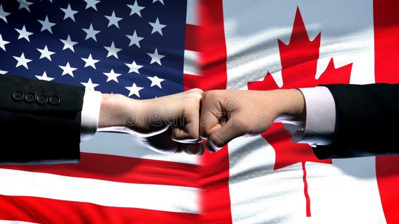 USA vs Kanada konflikt, stosunek międzynarodowy kryzys, pięści na chorągwianym tle zdjęcia royalty free